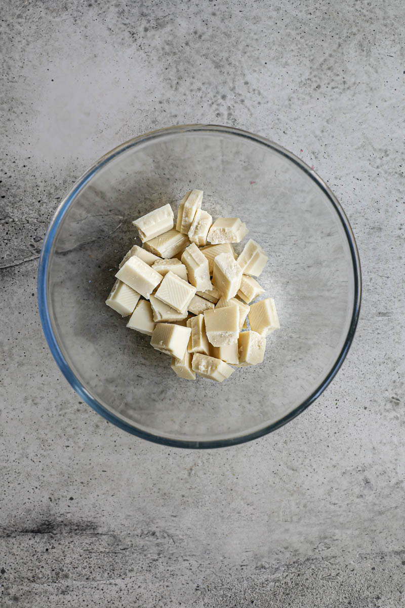 Making the white chocolate ganache cream filling: Chopped white chocolate in a glass bowl.