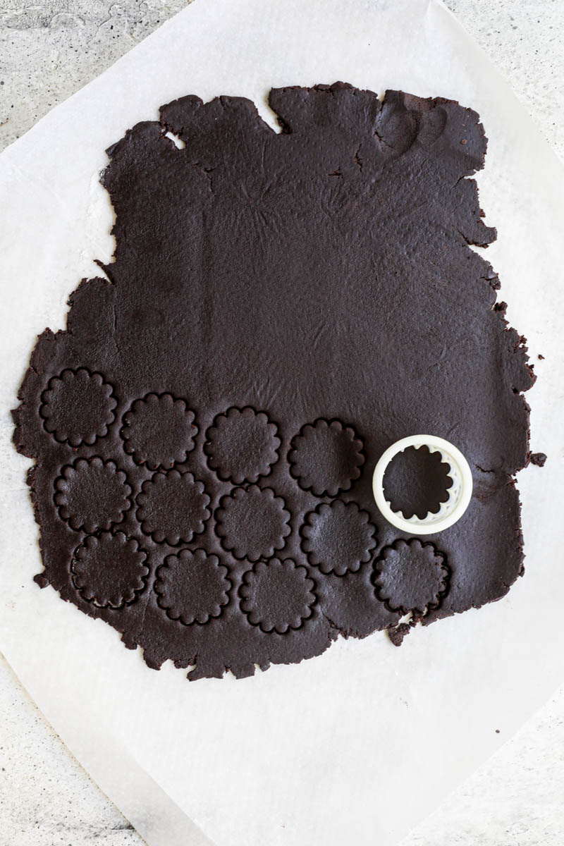 Shape and bake the homemade Oreo cookie: The rolled-out and cut out Oreo cookie dough on a piece of parchment paper.