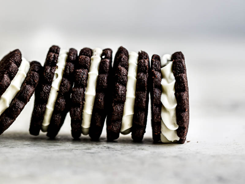 5 homemade Oreo cookies filled with white chocolate cream filling standing next to each other in the bottom part of the frame.