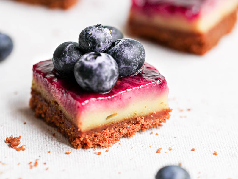 Closeup shot of one creamy square lemon bar with blueberry swirls and blueberries on top.