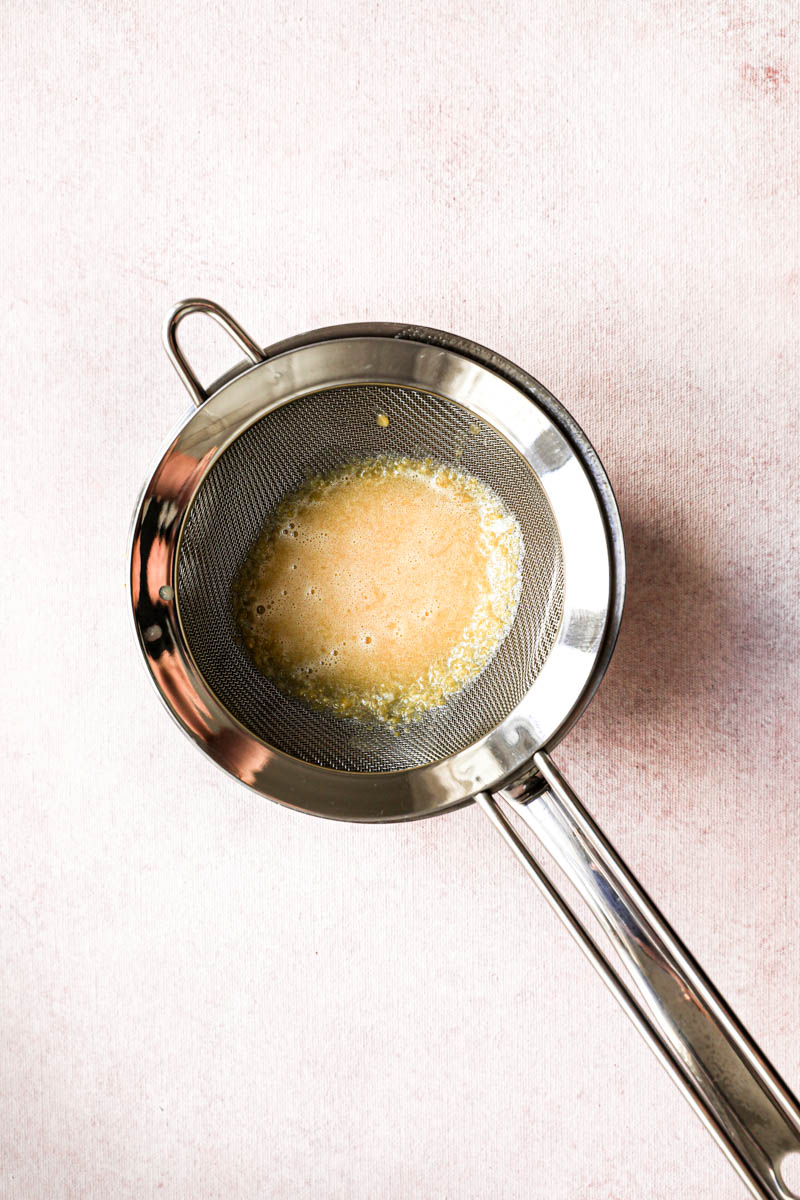 Making the lemon cream for the square lemon bars: straining the lemon cream into the small pan before bringing it to a boil.