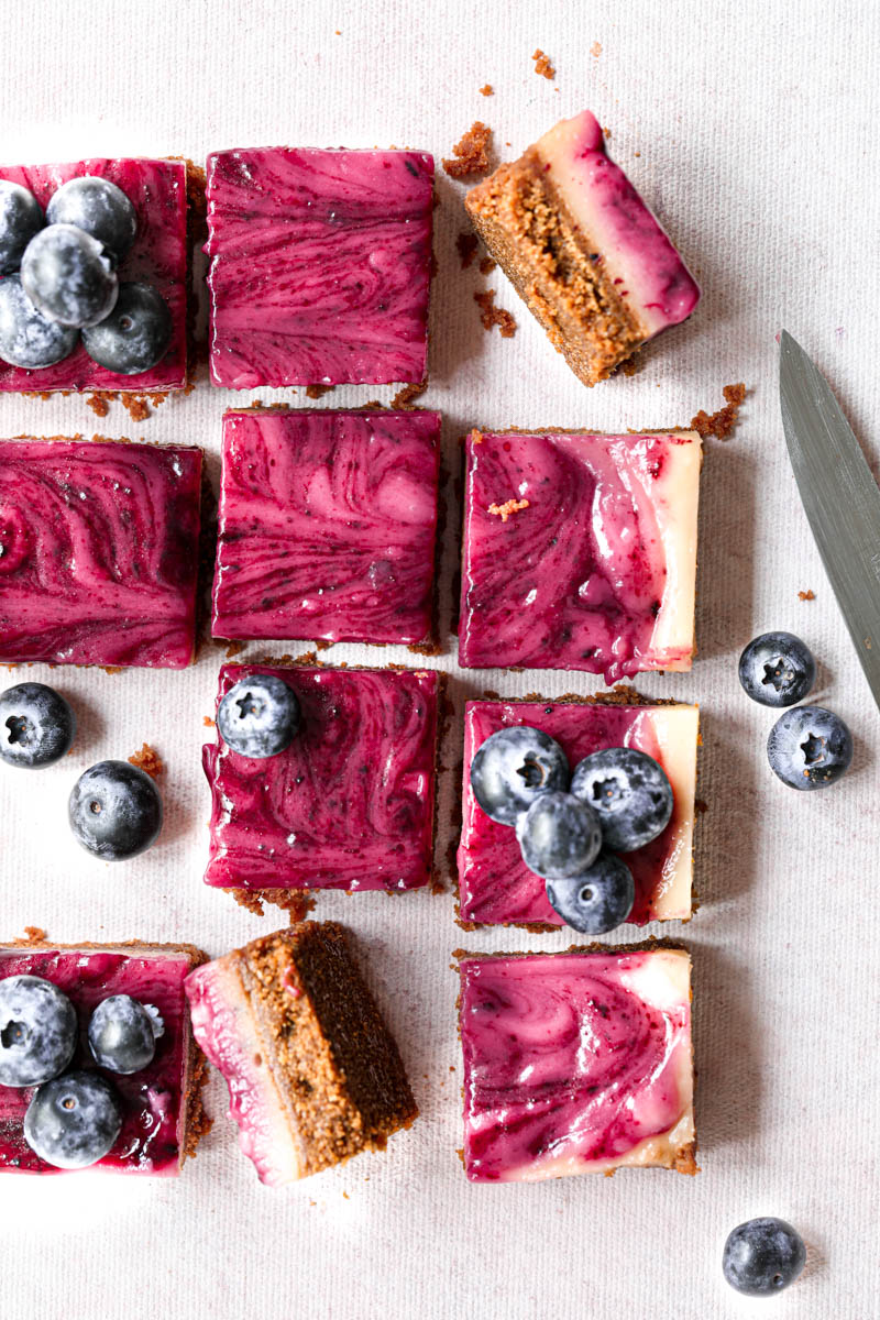 Overhead shot of all the blueberry lemon bars sliced into squares with a knife on the side over a pink backdrop.