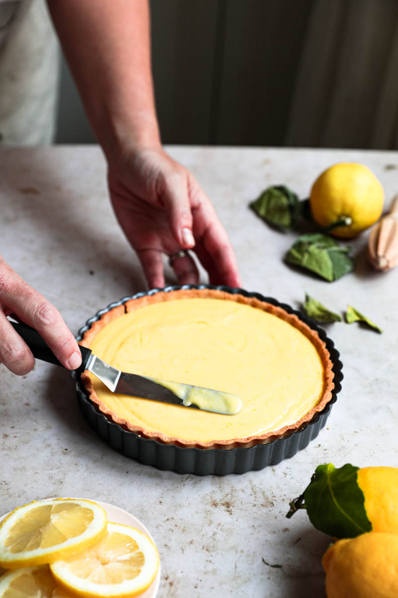 Two hands spreading the lemon curd on the tart using a small offset spatula.