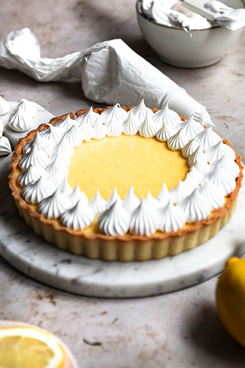 Lemon curd tart topped with swiss meringue kisses on a marble platter with a pipping bag behind the tart and some meringue kisses around.