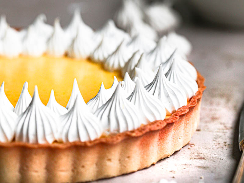 The lemon curd tart topped with swiss meringue kisses with small bowl and a spatula with meringue behind it and some meringue kisses around.