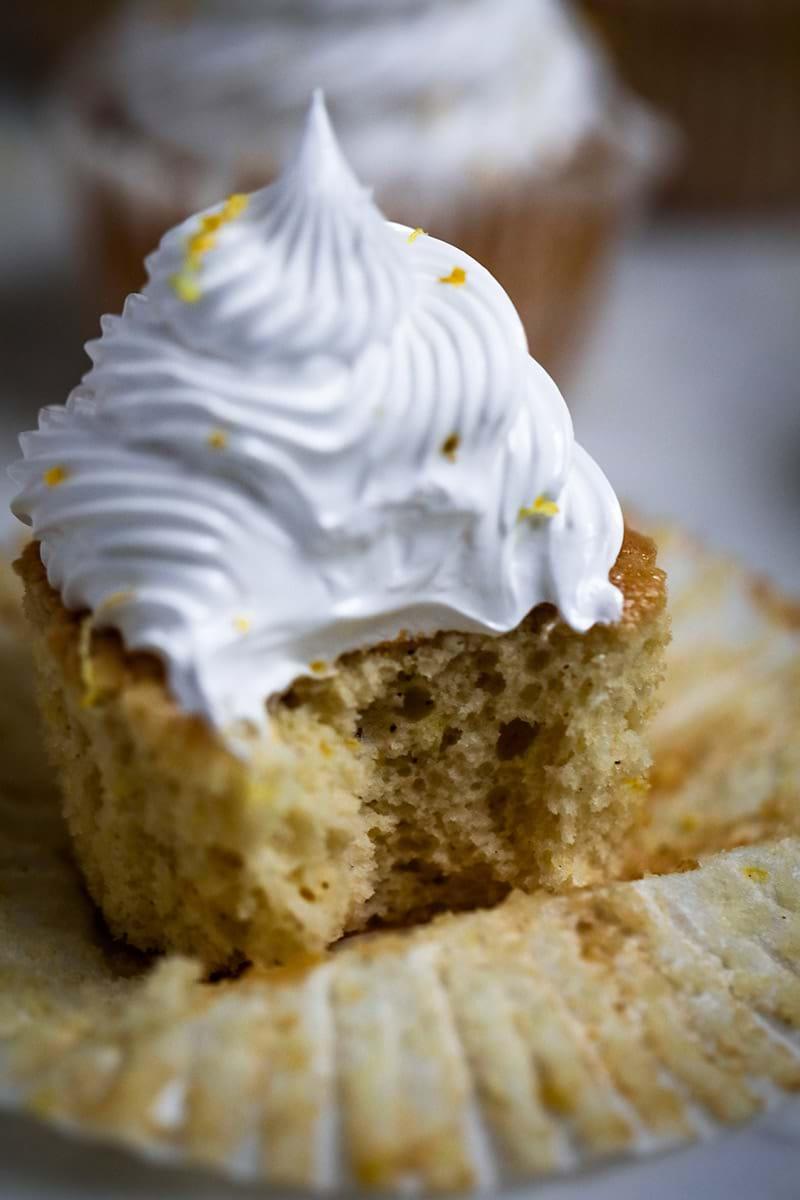 Closeup shot of one Lemon Meringue Cupcakes minus one bite