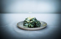 90° shot of the spinach malfatti on a plate with cream and parmesan cheese