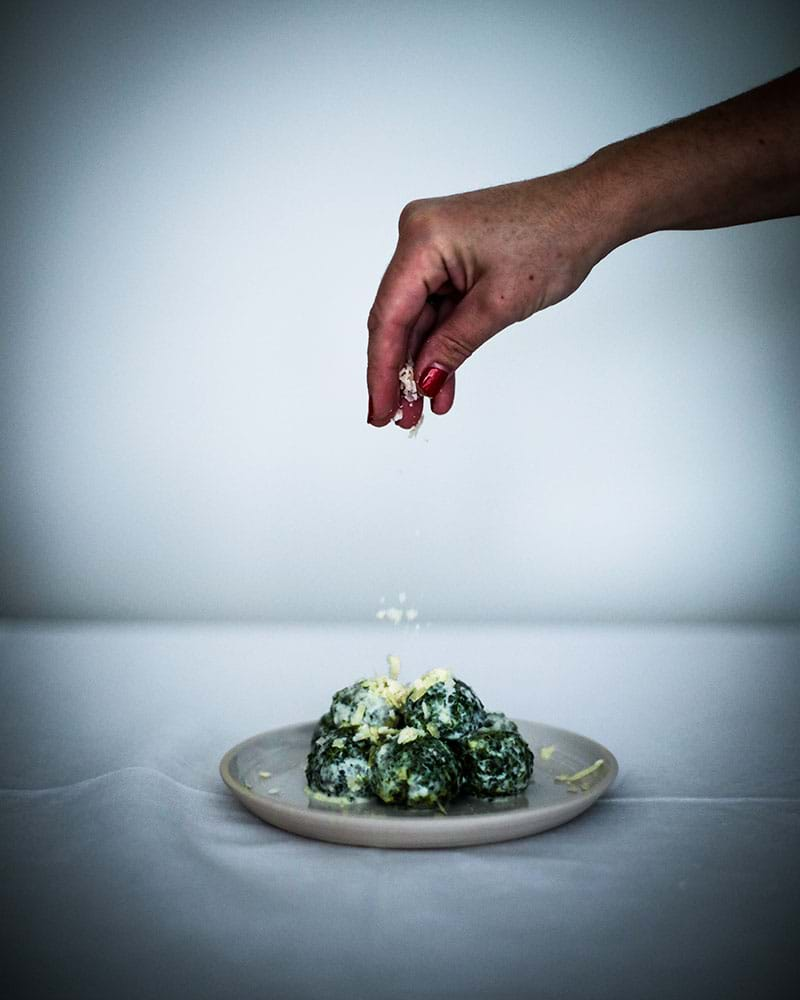 A hand sprinkling the malfatti with parmesan cheese