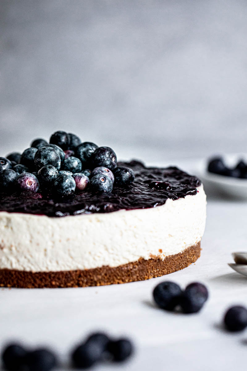 Closeup of the sliced no bake blueberry cheesecake with blueberry topping as seen from the side.
