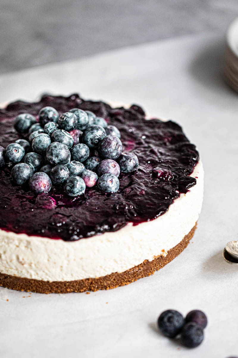 The whole fluffy no bake vanilla blueberry cheesecake with some blueberries on the front.