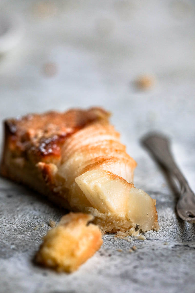 Closeup shot of one slice of the pear frangipane tart with a fork at the side