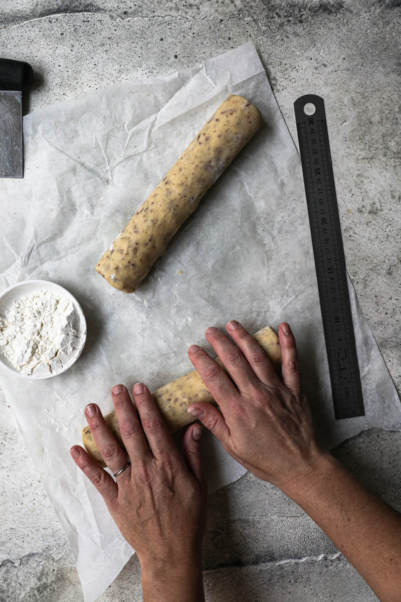 2 hands rolling the dough into the shape of a log