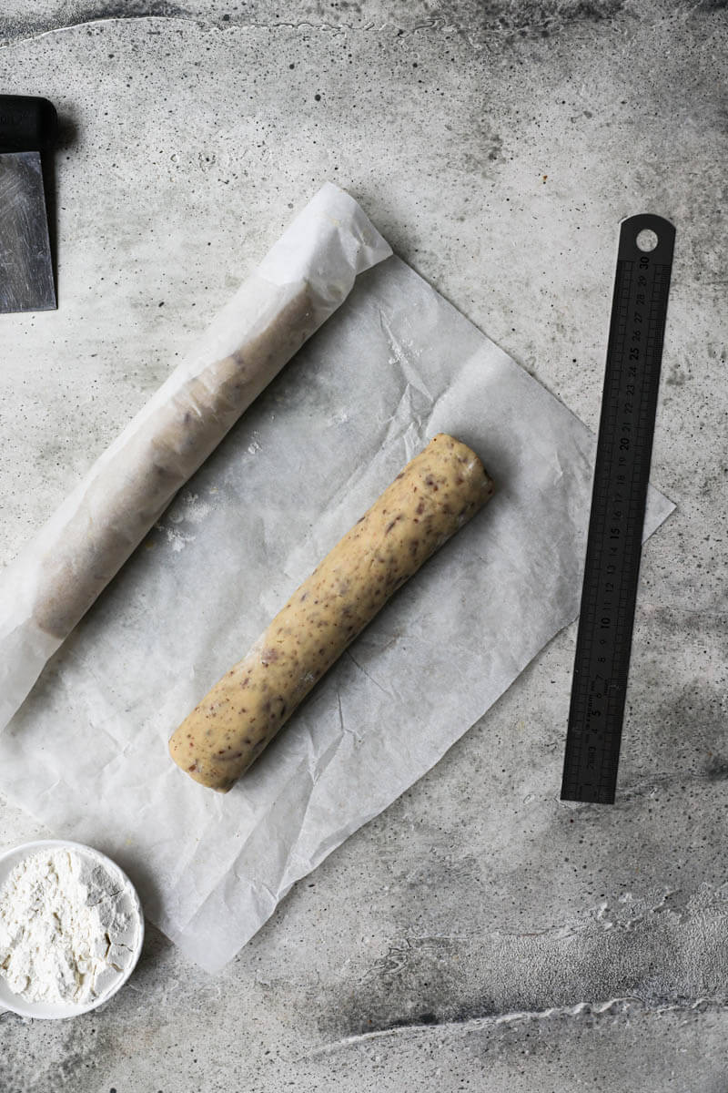 The cookie dough logs wrapped in parchment paper