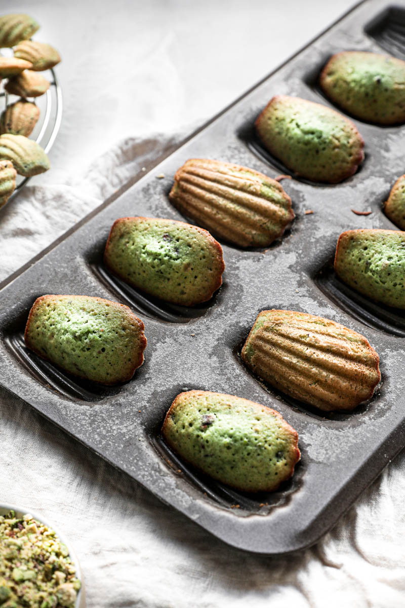 The baked pistachio madeleines inside the madeleine pan, turned 90 degrees with other madeleines on wire rack in the left top corner.