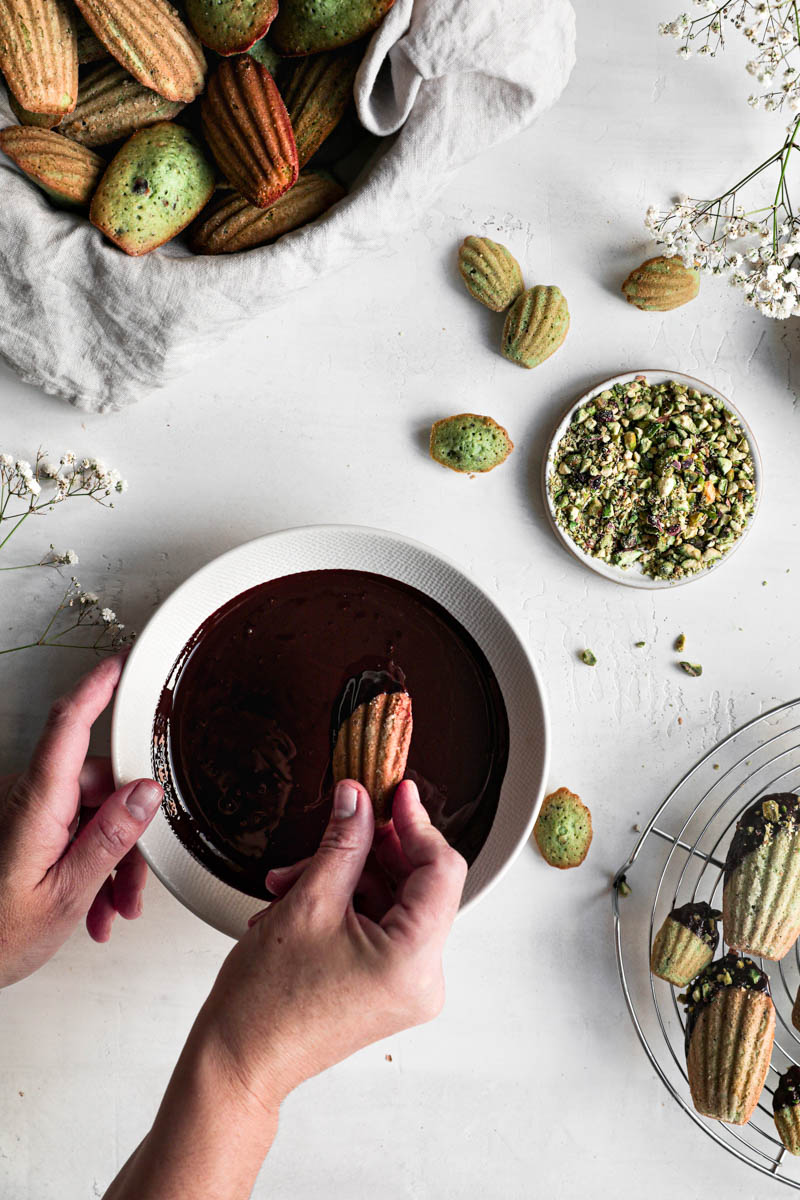 One hand dipping a madeleine inside a bowl of chocolate glaze with a wire rack filled with baked madeleines in the top left corner and plate full of grounded pistachio on the side.