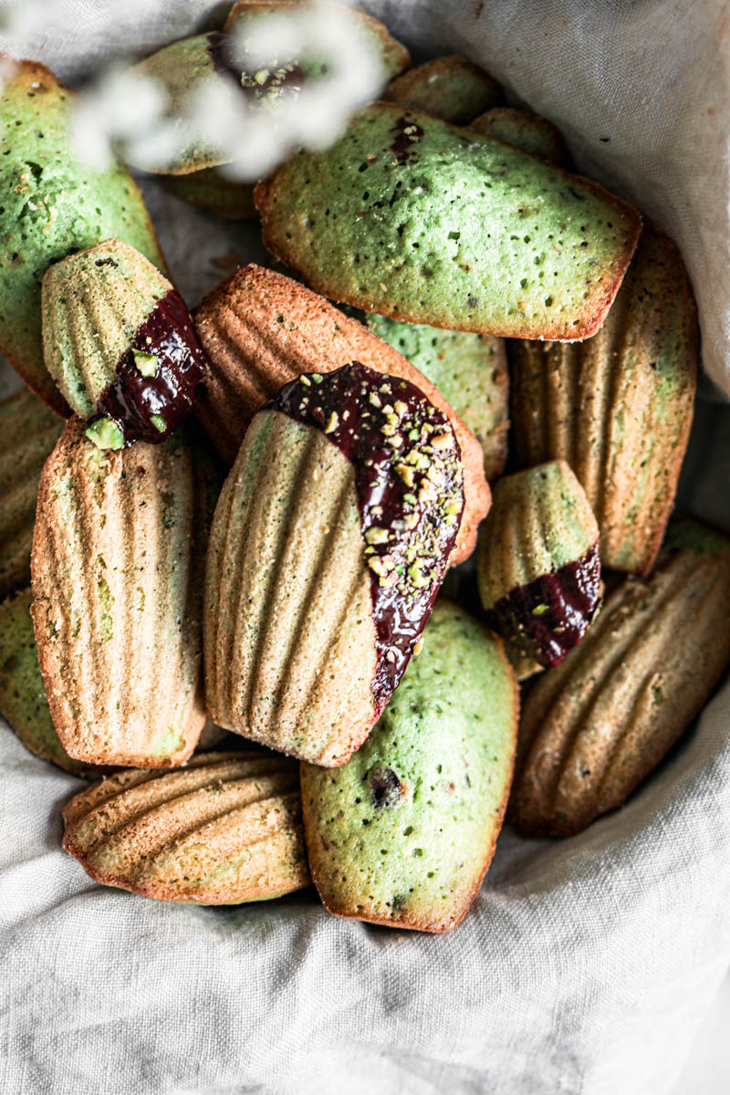 A basket covered in a beige linen holding the pistachio madeleines covered in chocolate glaze and pistachios as seen from above with some flowers blurry in the corner.