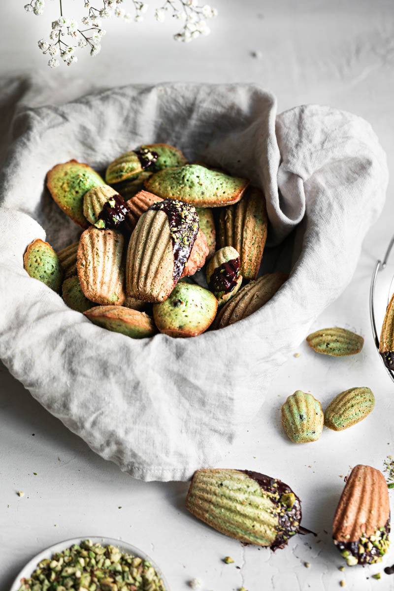 A basket covered in a beige linen holding the pistachio madeleines covered in chocolate glaze and pistachios and some madeleines surrounding the basket.
