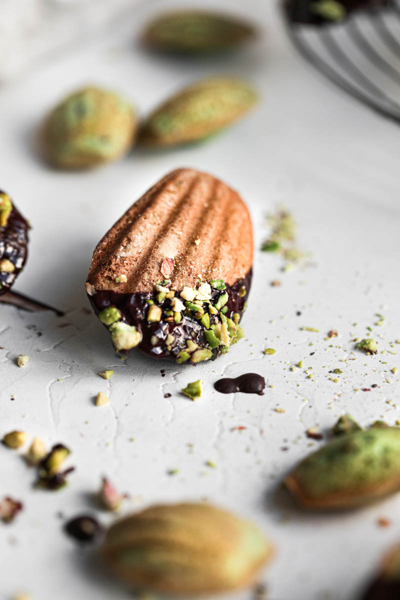 One pistachio French madeleine covered in chocolate glaze in focus at the center of the frame with other small madeleines around it.