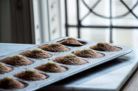 90° shot of pistachio madeleines in the tin in front of a French window