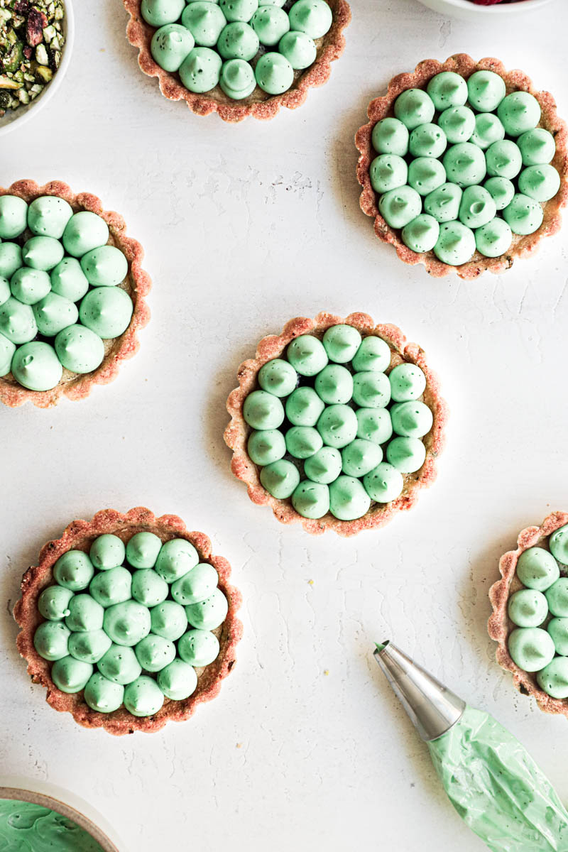 Pistachio raspberry white chocolate tartlets assembly: all the tartlets topped with white chocolate pistachio ganache kisses and a piping bag on the side.