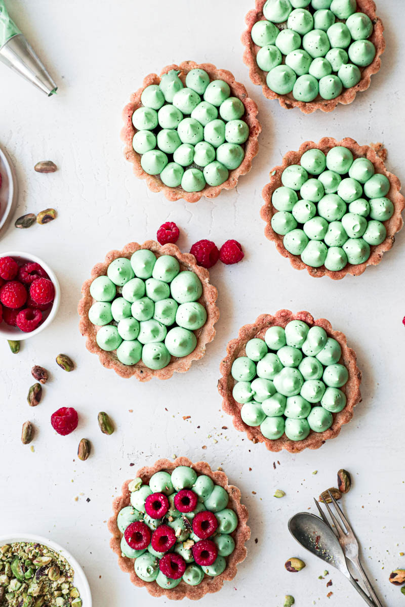Pistachio raspberry white chocolate tartlets assembly: one tartlet topped with fresh raspberries and the other five only with ganache kisses.