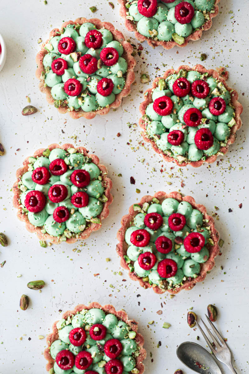 Pistachio raspberry white chocolate tartlets assembly: the tartlets topped with fresh raspberries filled with raspberry jam.