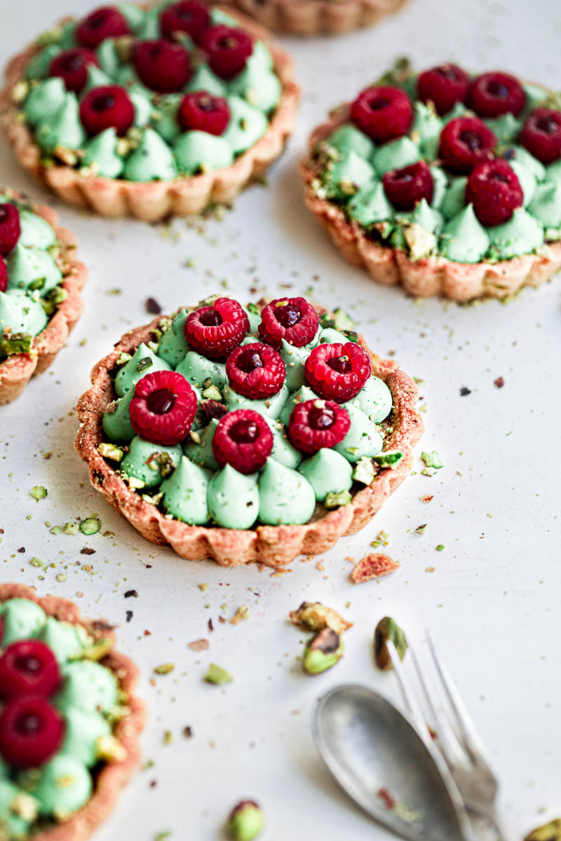 The pistachio raspberry white chocolate tartlets assembled topped with fresh raspberries seen from the side.