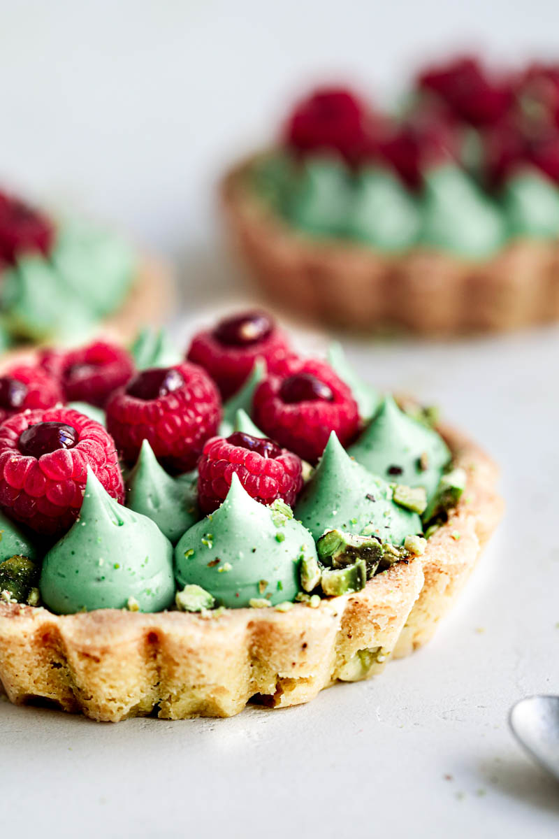 Closeup of 1 pistachio raspberry white chocolate tartlet with two others blurry in the back.