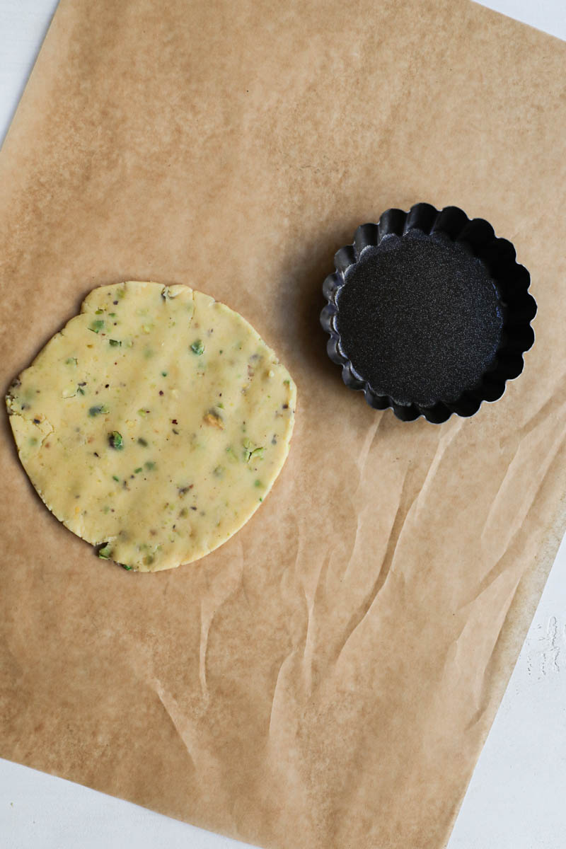 One piece of rolled crust cut in a small disk and the tartlet tin on the side.