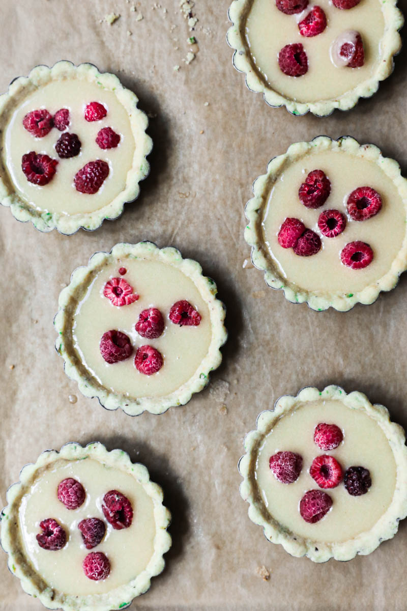 The tartlet tins lined with the pistachio shortbread crust filled with the financier topped with some raspberries.
