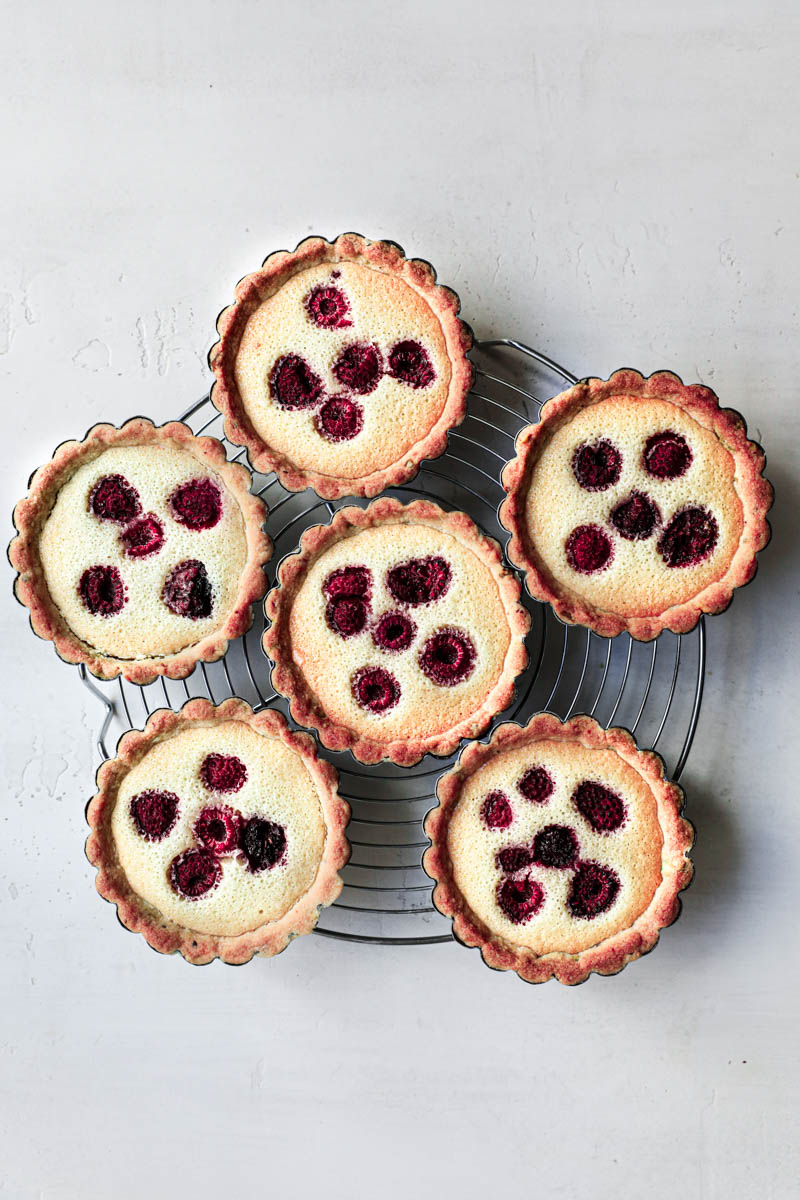 The baked pistachio raspberry tartlets on a round wire rack.