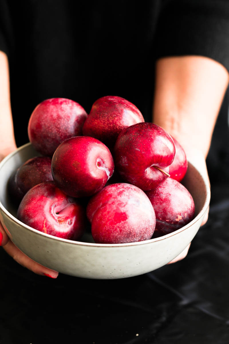 90° shot of 2 hands holding a bowl with fresh plums
