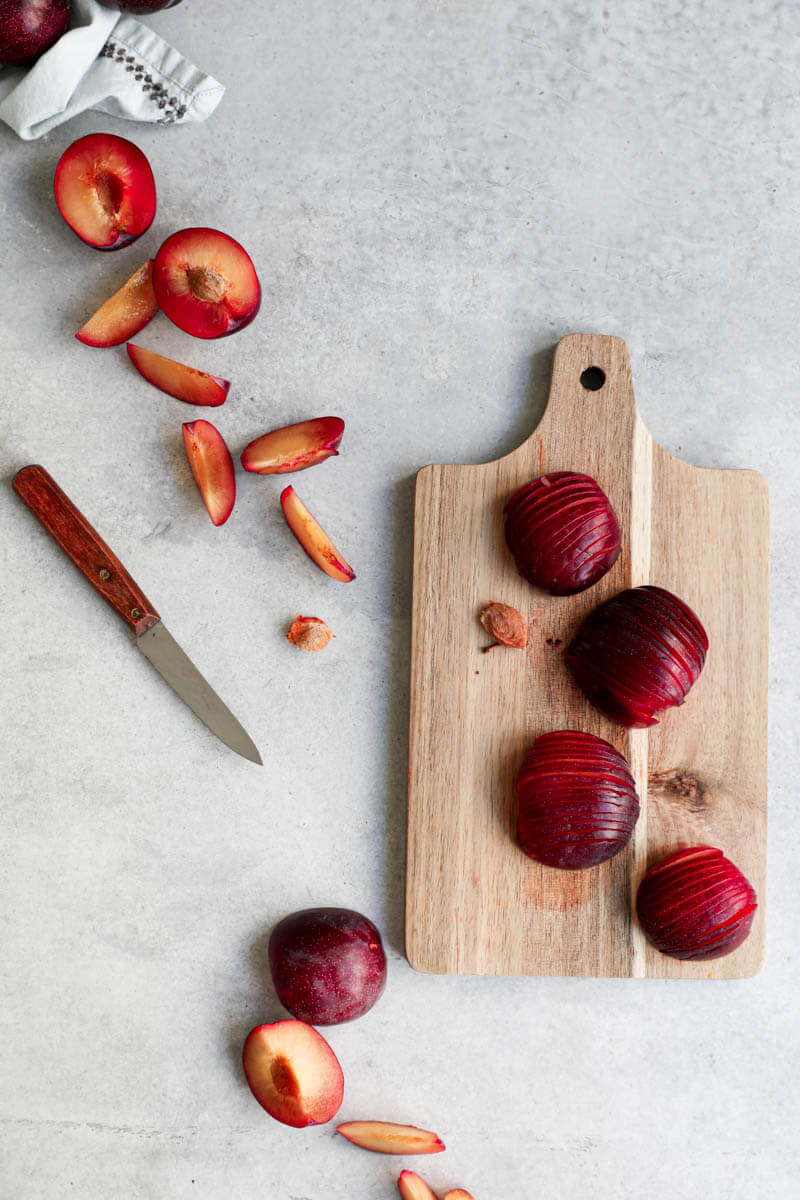 Overhead shot of sliced plums on a wooden chopping board