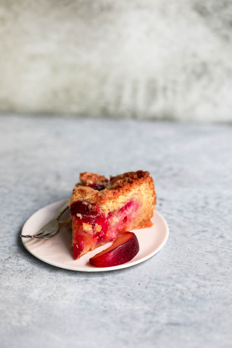 45° shot of a slice of plum cake on a plate
