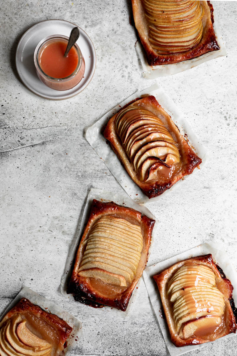 Overhead shot of the puff pastry apple tarts with a pot of salted caramel in the top left corner