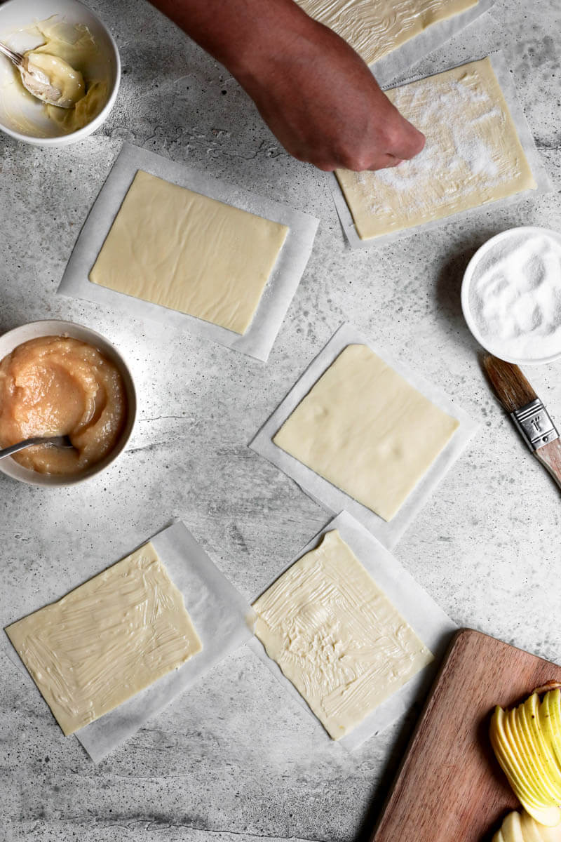 Overhead shot of the puff pastry rectangles with a hand sprinkling sugar over them