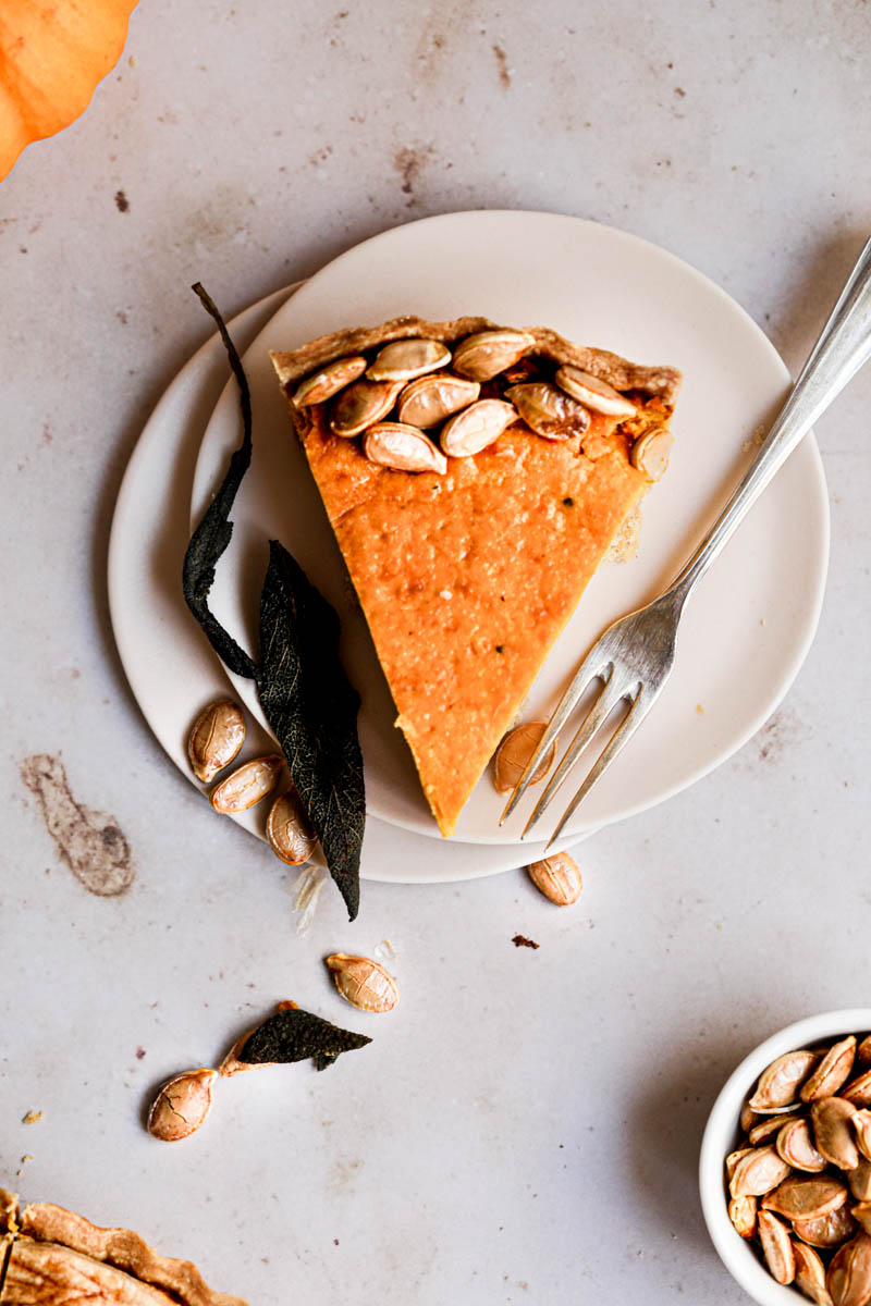 A piece of savory pumpkin pie on a pink plate with a fork on the side and the corner of the quiche in the bottom left corner.