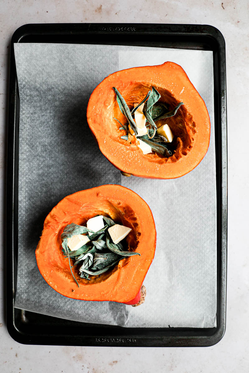 Making the pumpkin quiche filling: a pumpkin cut in 2 on a baking tray lined with parchment paper, each filled with sage and butter.