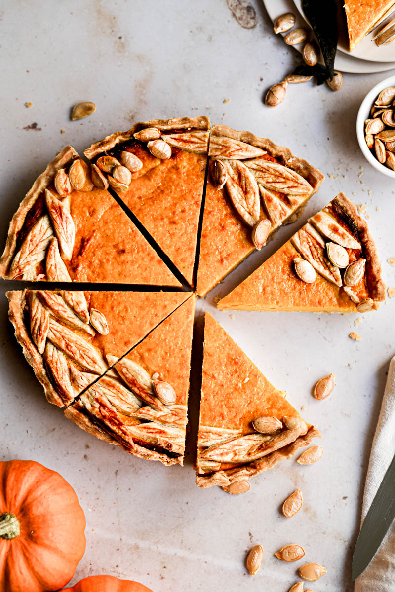 The sliced pumpkin ricotta quiche seen from above, with a plate and a pumpkin slice in the top right corner.