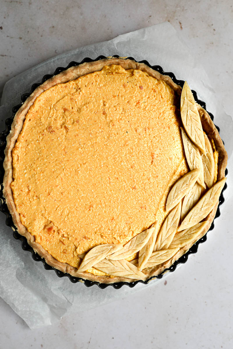 The pumpkin quiche filled and topped with the pastry dough leaves.