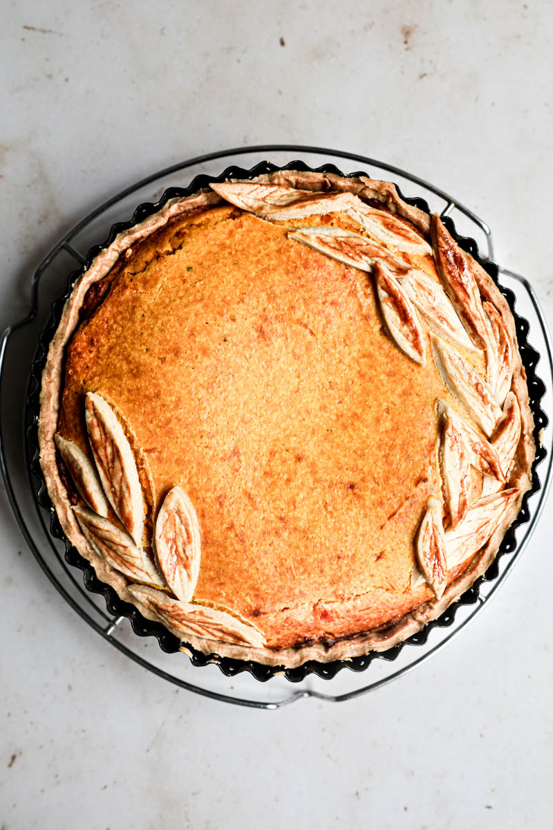 The baked savory pumpkin pie inside the tin placed on wire rack.