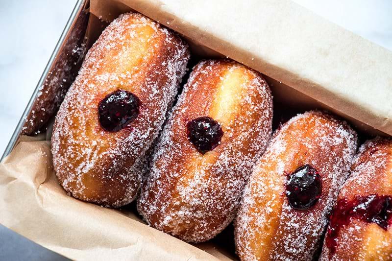 Overhead closeup shot of raspberry filled doughnuts inside a cake pan