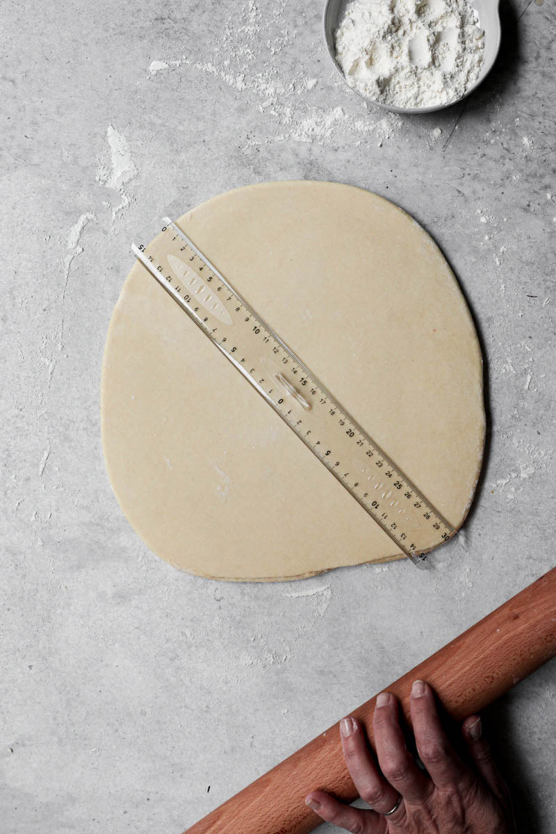 The rolled-out brioche donut dough with a ruler on top.