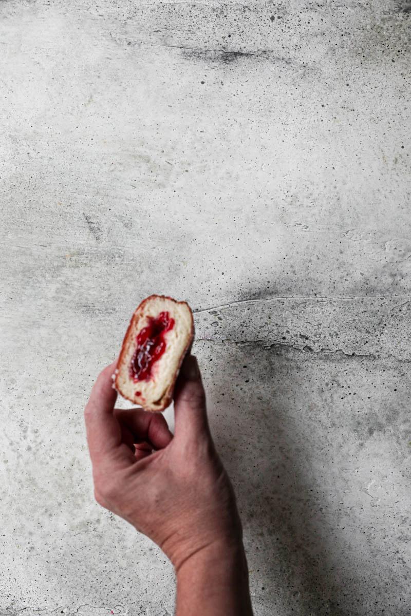 A hand holding a sliced filled raspberry jam brioche donut.
