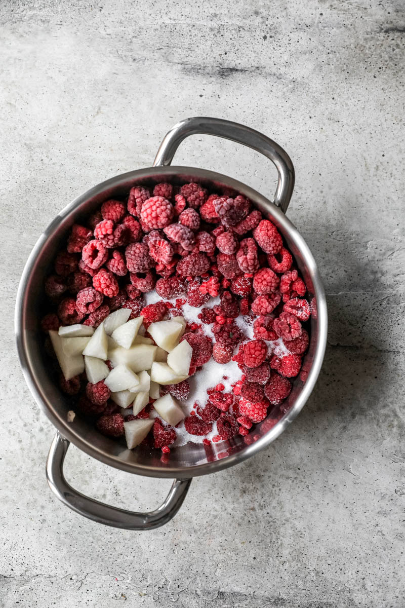 A big pot with frozen raspberries and sliced pear.