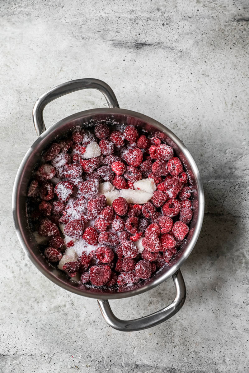 A big pot with the frozen raspberries and sliced pear mixed with the sugar.