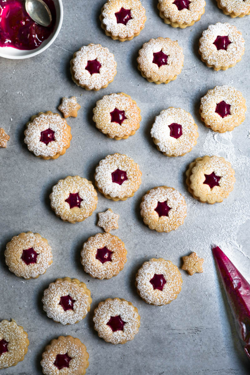 Linzer cookie bottoms filled with raspberry jam toped with the linzer cookie top