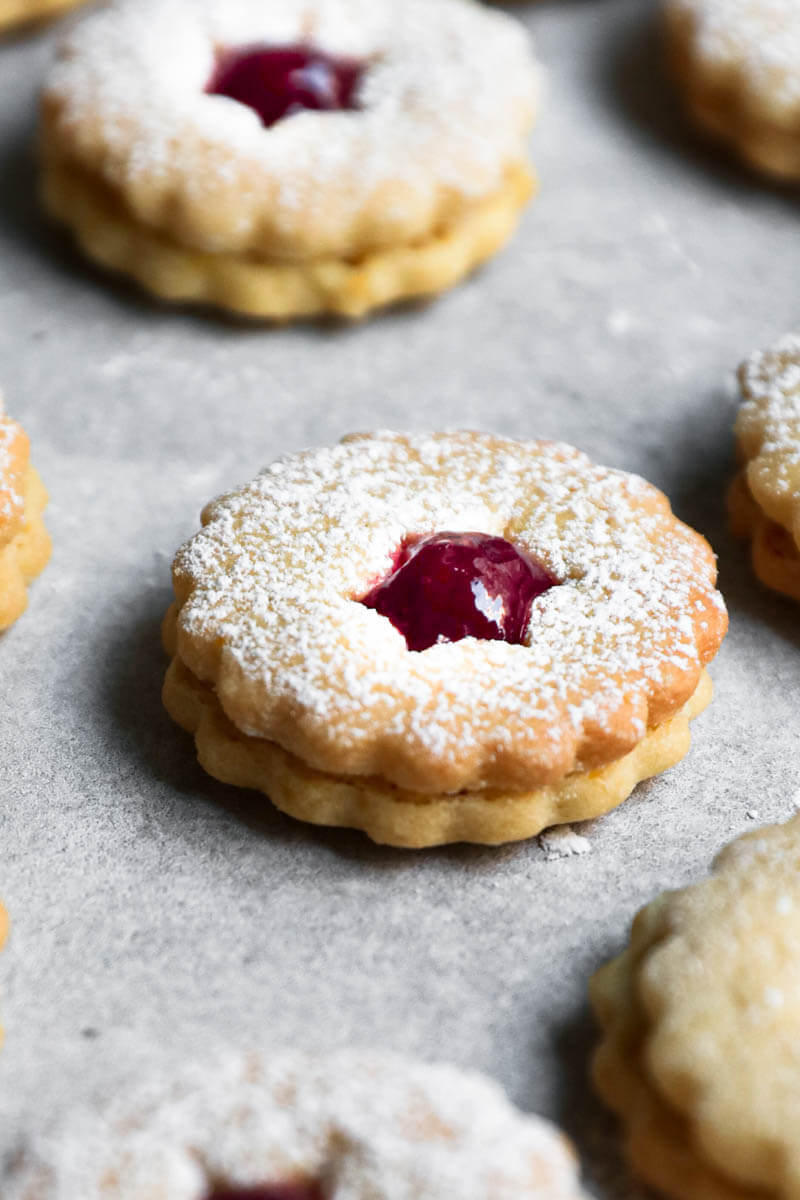 One linzer cookie filled with raspberry jam, with other blurry all around