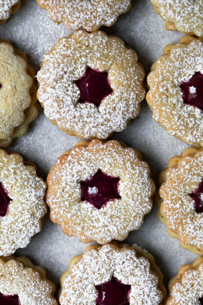 Linzer cookies filled with raspberry jam arranged in lines