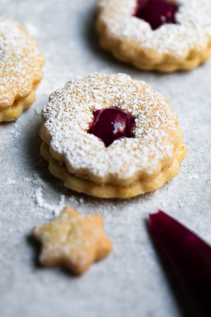 One linzer cookie filled with raspberry jam, with other blurry behind and a piping bag in the bottom right corner